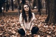 Sad girl leaves park trees fall