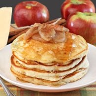 A stack of golden buttermilk pancakes with baked apple topping and syrup.