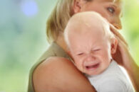 child falls crying in moms arms