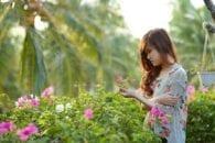 Emotional girl pregnant garden flowers