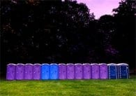 Repeated porto-potties, dusk, purple sky, green grass