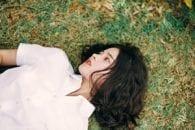 White shirt black hair green brown grass girl worried emotional