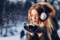 Woman ear muffs mittens blowing snow