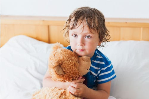 little boy sad and alone in bed
