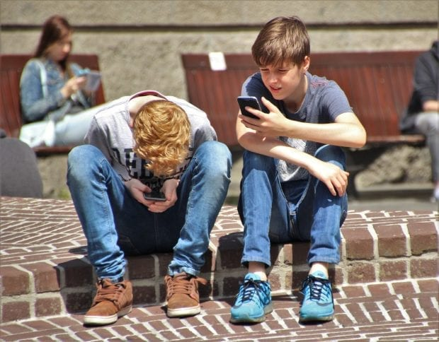 two teenage boys sitting on cell phones