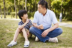 Father giving advice to his son while sitting on the grass at the park