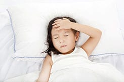 Girl laying on white pillow and sheets not feeling well