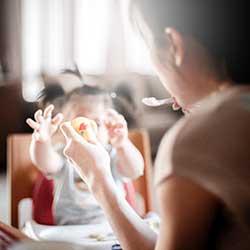 mother feeding baby safe finger foods